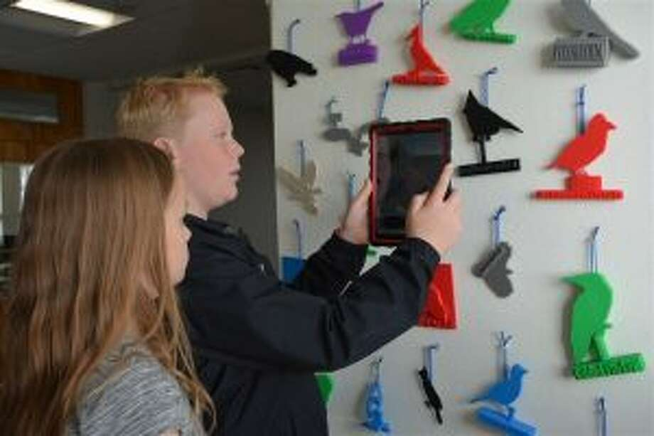 Bird studies recently took flight at New Canaan Country School. New Canaan Country School sixth graders Waverly Walters and Ned Smith, both of New Canaan, demonstrate the Augmented Reality experience they created as part of their scientific study of birds. — Contributed photo