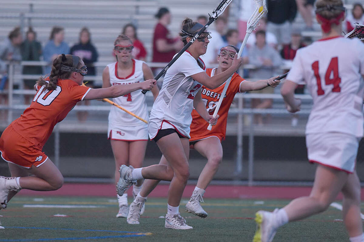 New Canaan's Lauren Bisceglia drives to the Ridgefield net during the Rams' 8-5 win in the CIAC Class L semifinals Monday night at Brien McMahon High School. - Dave Stewart/Hearst Connecticut Media