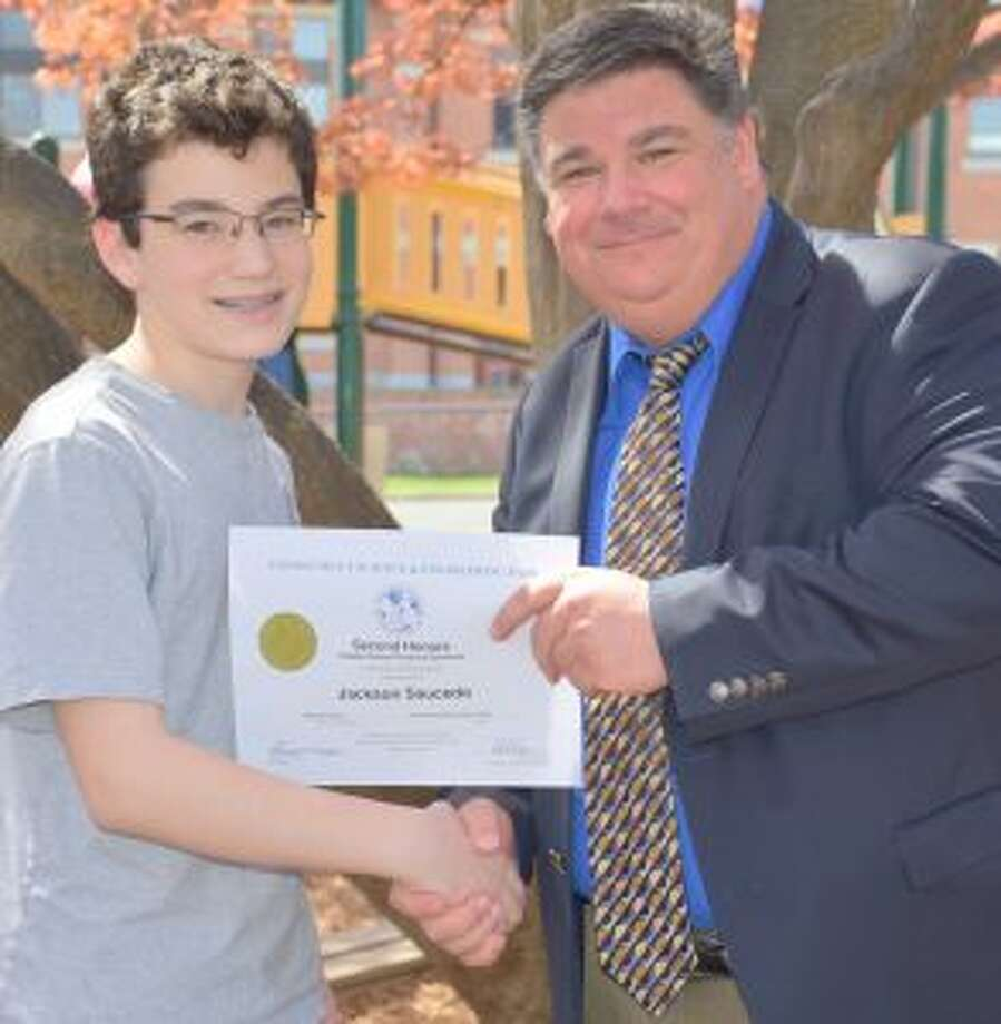An Odyssey student from St. Aloysius School in New Canaan is heading to the World Championships. Superintendent of Schools Dr. Steven F. Cheeseman awards Jackson Saucedo a certificate of achievement. — Contributed photo