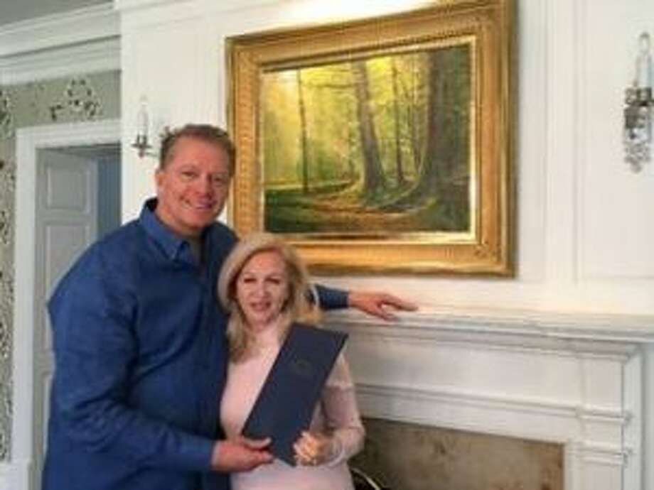 "Dave and Deb Checketts in front of a picture of the ""sacred grove"" at their home holding the actual folder containing their mission designation."