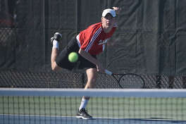 New Canaan co-captain Luke Crowley follows through on a serve. - Dave Stewart photo