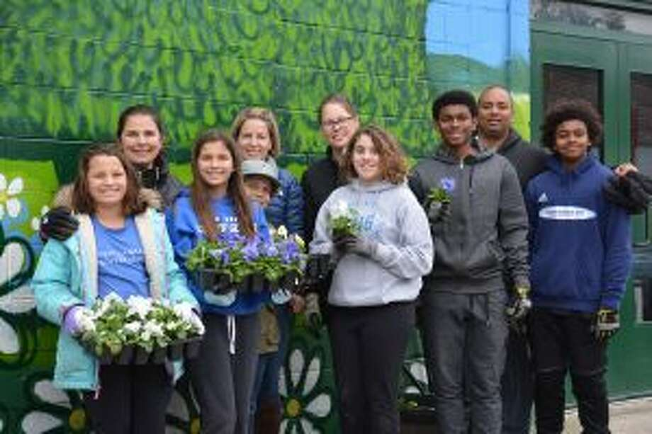 "An Annual ""Day of Service"" at New Canaan Country School (NCCS), remembered a classmate. From left, Christina, Rochelle and Katey Charnin of Darien; Billy and Sanny Warner of New Canaan; Mary and Anna Majewski of Darien; Desmond '17; and Dan and Mason Pratt of Trumbull, planted flowers at Open Door Shelter of Norwalk. — Contributed photo"