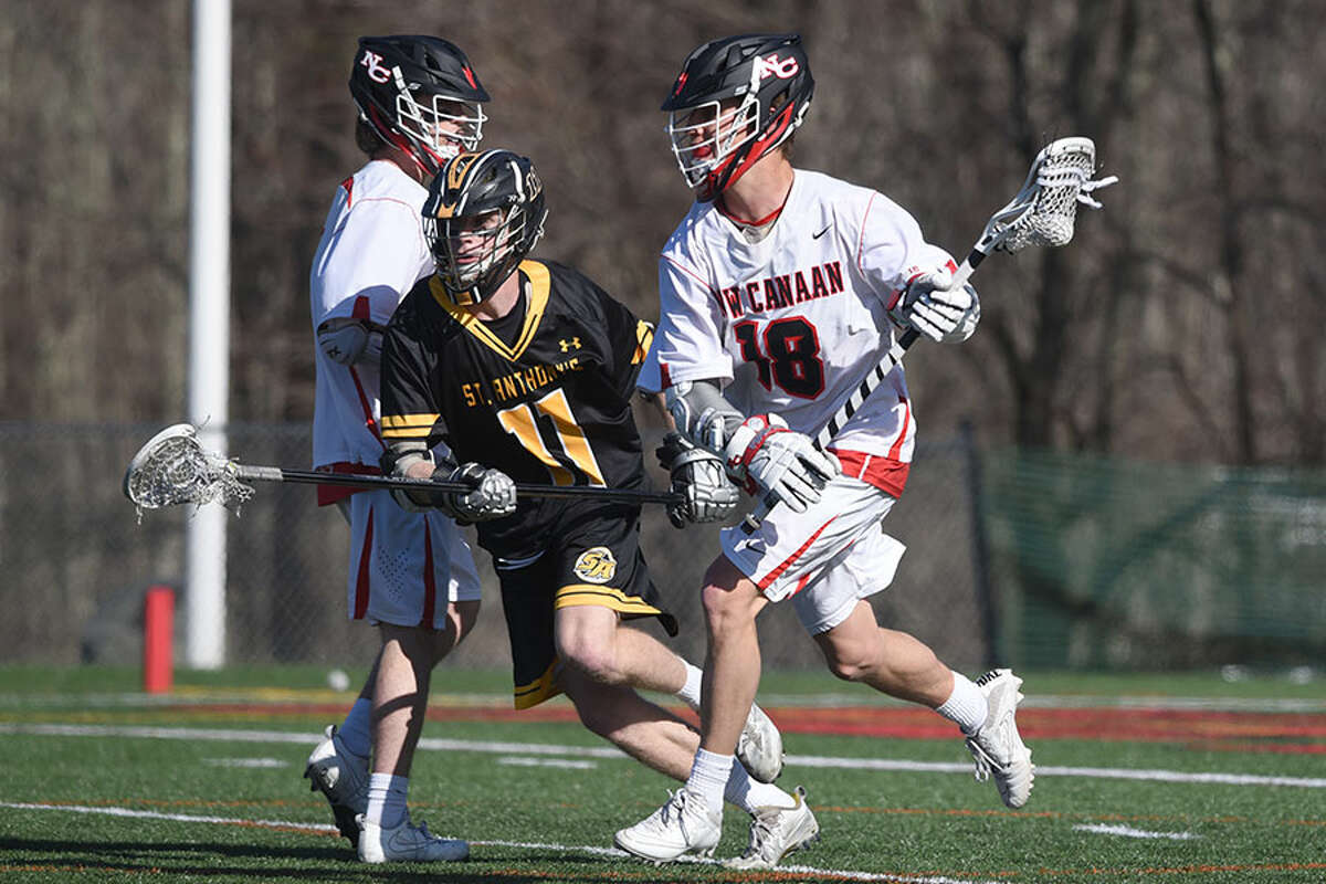 New Canaan senior co-captain Mac Deane (18) looks for room while St. Anthony's Brady Keneally (11) defends. - Dave Stewart photo