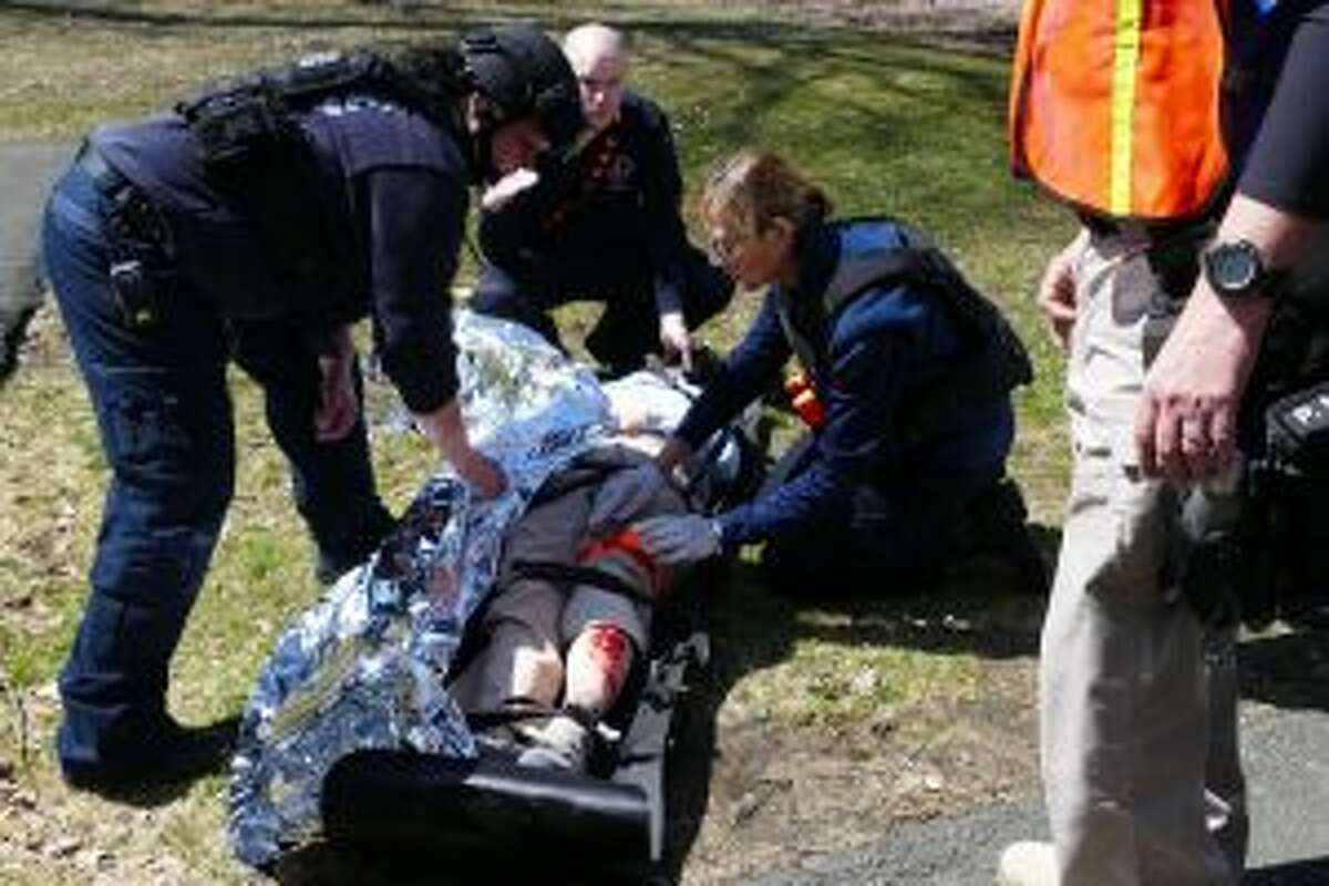 At the drill, Norwalk paramedic Abigail Woodhouse is leaning over the 'victim', New Canaan EMT Stephanie Dalia is kneeling by her and New Canaan firefighter Mike Sasser looks on in the background. - Grace Duffield photo
