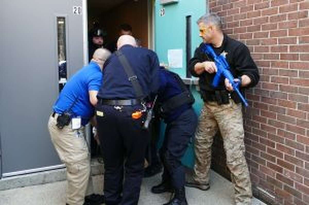 During a New Canaan emergency training exercise, Patrol Officer and Saxe Middle School Resource Officer, Jeff Deak, is standing with a rifle by the back door of East School. The drill is part of a program called the Medical Preparedness and Response to Dynamic Incidents (MPaRDI). - Grace Duffield photo
