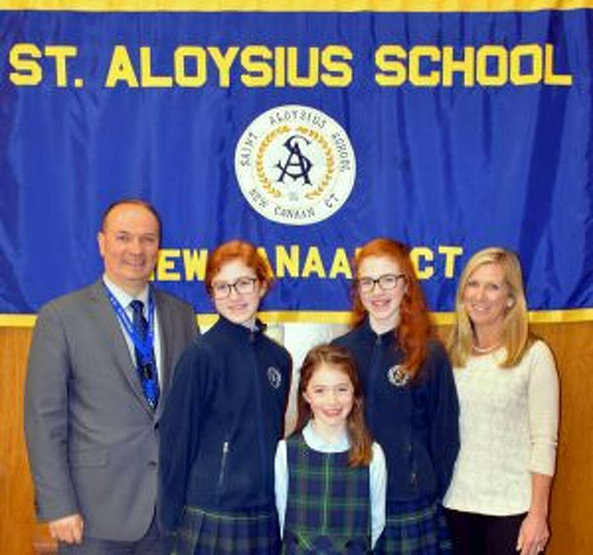 New Canaan: St. Aloysius's 'Read to Feed' in Lent shined light on the Heifer Project. Principal Bardhyl Gjoka and Read To Feed Coordinator Deborah Moran, reward winners in the student contest Anna Gayer, left; Noelle Gayer, right; and Lilly Gayer, front. - Contributed photo