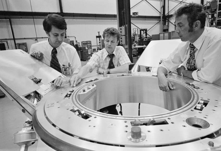 July 10, 1974) --- Three Apollo-Soyuz Test Project (ASTP) engineers look over a Soyuz spacecraft docking system prior to an ASTP docking mechanism fitness test conducted in Building 13 at the Johnson Space Center (JSC). They are (left to right) Robert White, Vladimir Syromyatnikov and Yevgeniy Bobrov. White is the American chairman of ASTP Working Group Number 3, and Syromyatnikov is his Soviet counterpart. This working group is concerned with ASTP docking problems and procedures. White is with JSC's Spacecraft Design Division. Syromyatnikov is senior researcher of the Soviet State Research Institute of Machine Building. Bobrov is a junior researcher with the Institute of Machine Building. The joint United States - USSR ASTP docking mission in Earth orbit is scheduled for the summer of 1975. (NASA)