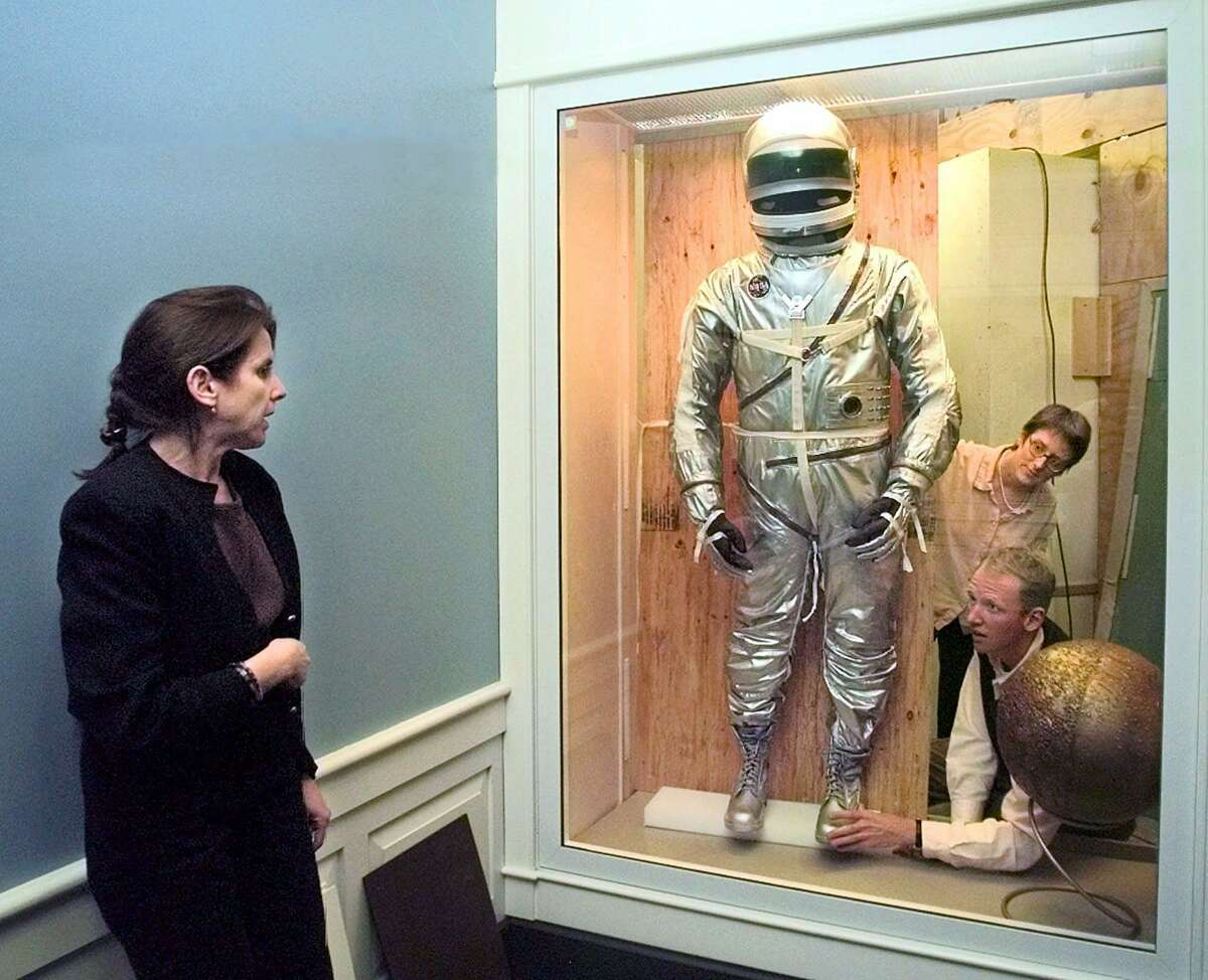Amy Forman, exhibition designer at the John F. Kennedy Library and Museum, left, directs assistant curator James Wagner, left, and Pat Silence, center, in positioning a recreation of the space suit worn by astronaut John Glenn during his 1962 'Friendship 7' obital space flight, Tuesday night, Oct. 20, 1998, at the museum in Boston. The Kennedy Museum will open a new exhibit with materials from their Glenn collection Saturday in honor of his upcoming space shuttle mission.