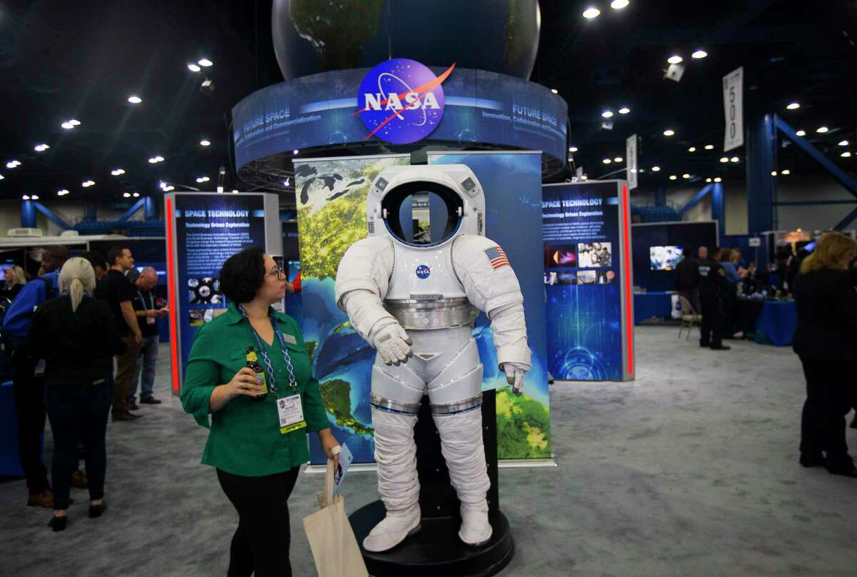 Visitors walk through SpaceCom's exhibit floor during an opening reception at the George R. Brown Convention Center, Tuesday, Dec. 5, 2017, in Houston.