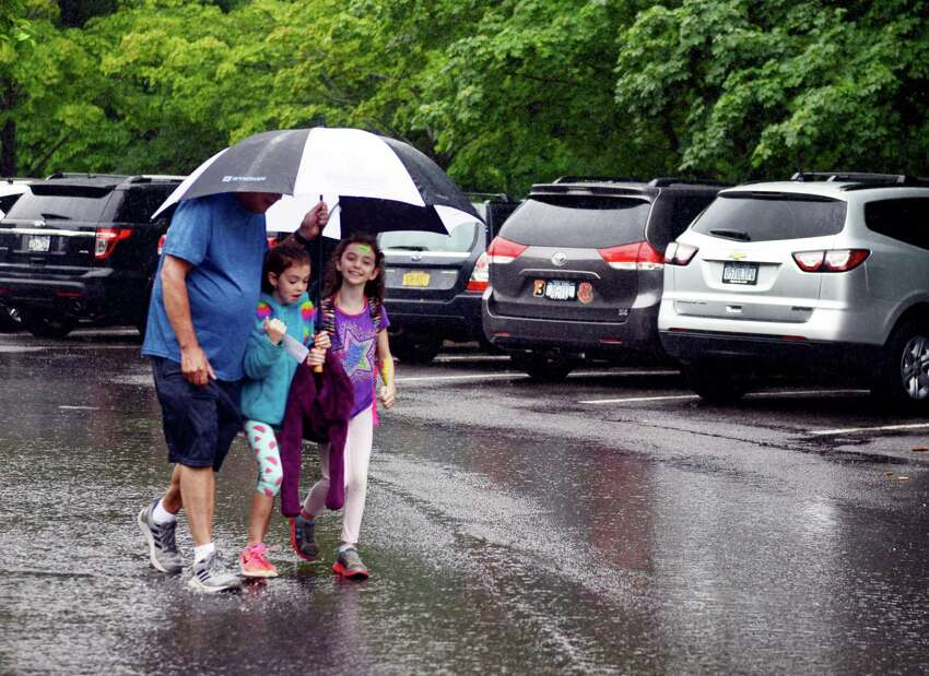 From left, Paul Garrison walks his grandchildren, Ally and Sophie Barnette, both 9, from Hamagrael Elementary School after early dismissal on Tuesday, June 25, 2019, in Bethlehem, N.Y. (Catherine Rafferty/Times Union)