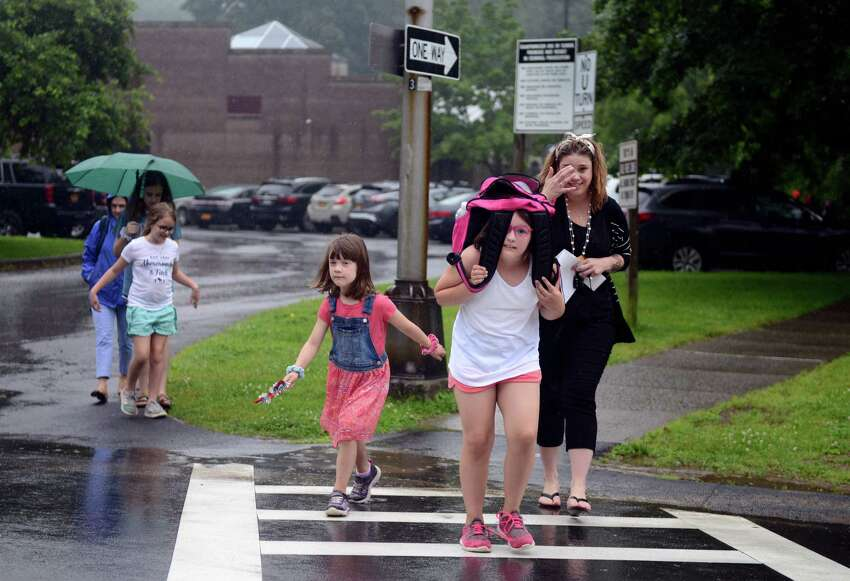 Emily Dunn, 6, center left, and Maddie Dunn, 9, center, and their mother Connie Dunn, right, run from the rain after early dismissal from Hamagrael Elementary School on Tuesday, June 25, 2019, in Bethlehem, N.Y. (Catherine Rafferty/Times Union)