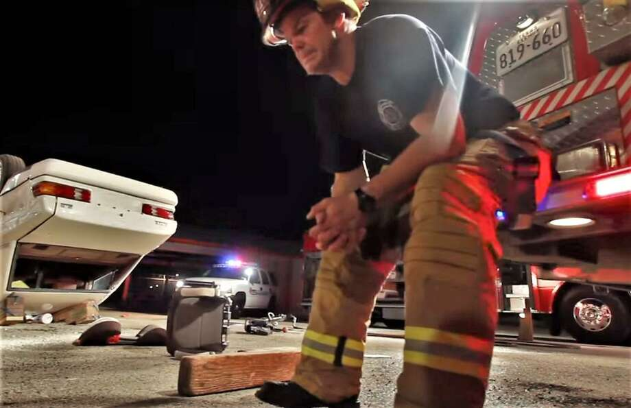 A firefighter sits near the scene of a critical incident in a public service announcement video on the Emergency Chaplain Group website. Photo: Courtesy Of The Emergency Chaplain Group