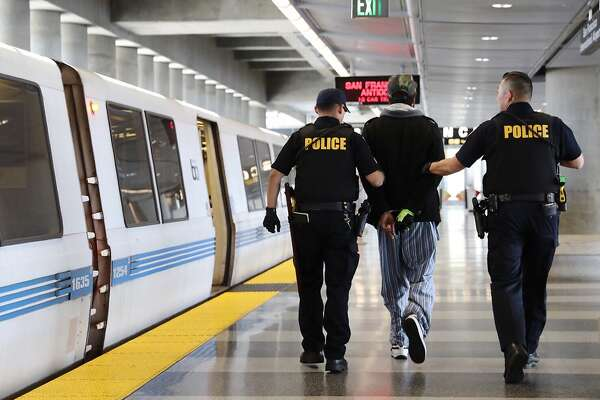 A homeless man is detained by BART police officers inside the SFO Airport BART station in South San Francisco, Calif. Wednesday, May 29, 2019.
