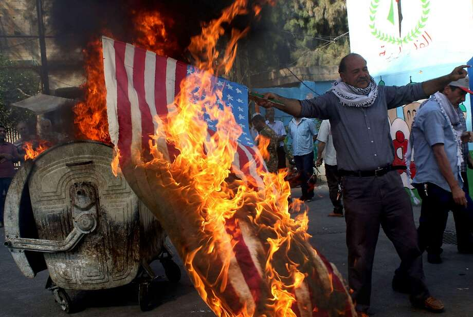 Palestinian refugees in Lebanon's southern Ain el-Helweh camp burn the U.S. flag in protest. Photo: MAHMOUD ZAYYAT;Mahmoud Zayyat / AFP / Getty Images
