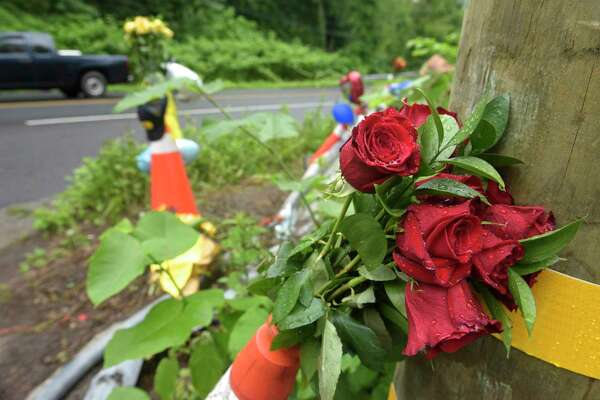 Flowers left at a roadside memorial at the site of an early Sunday morning fatal crash. Tuesday, June 25, 2019, in Newtown, Conn.