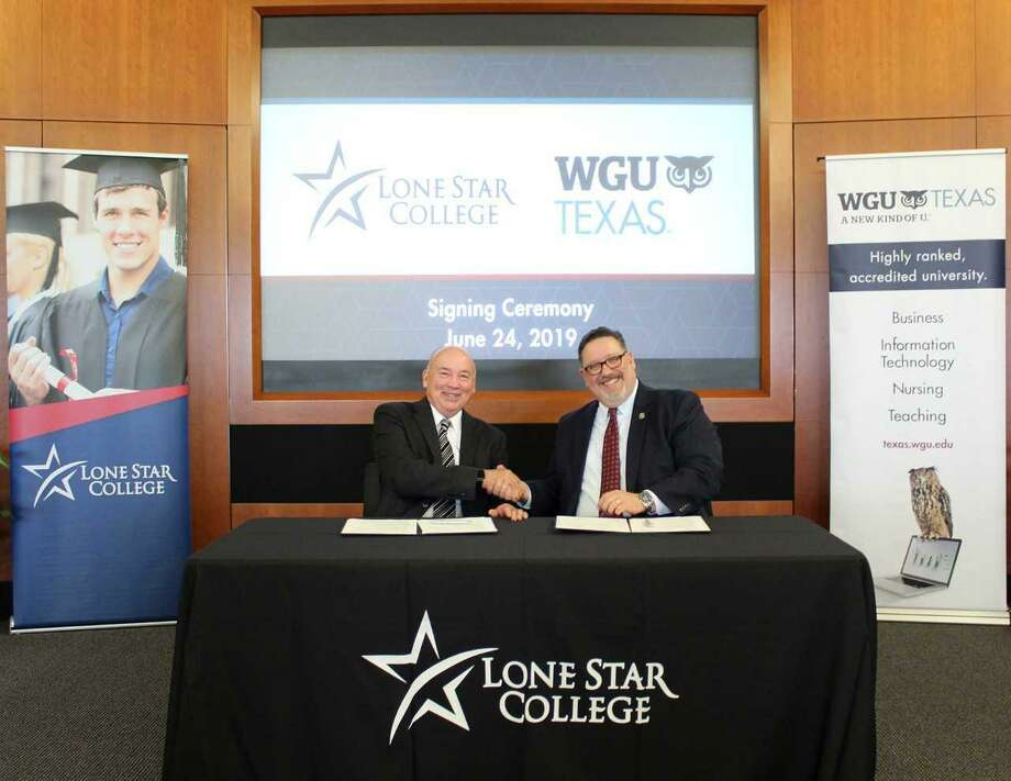Western Governors University, also known as WGU Texas, has entered into a partnership with Lone Star College and San Jacinto College. Here, WGU Chancellor Steven Johnson (right) signs the partnership with LSC Chancellor Steve Head. Photo: Submitted Photo / Submitted Photo