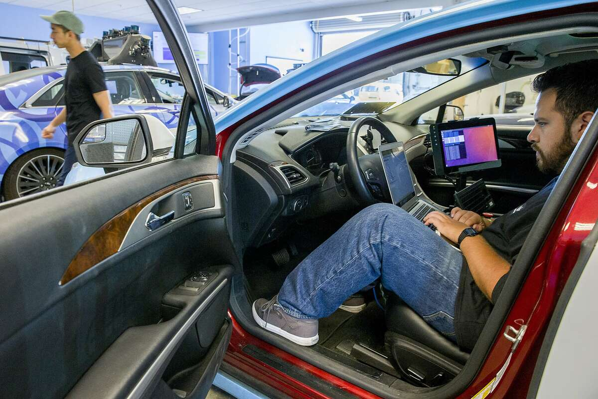 Martin Vega, right, checks the software of the self driving vehicle at drive.ai on Wednesday, Aug. 9, 2017, in Mountain View, Calif. Drive.ai is a Silicon Valley startup that's creating artificial intelligence software for autonomous vehicles.