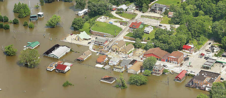 Downtown Grafton, including the intersection of Illinois 3 and 100, left, were under water Tuesday, June 4, as the village — like many along the Mississippi and Illinois rivers this spring — battled flooding. A river advocacy group on Tuesday estimated repairs and cleanup following this year's floods will cost communities more than $2 billion.