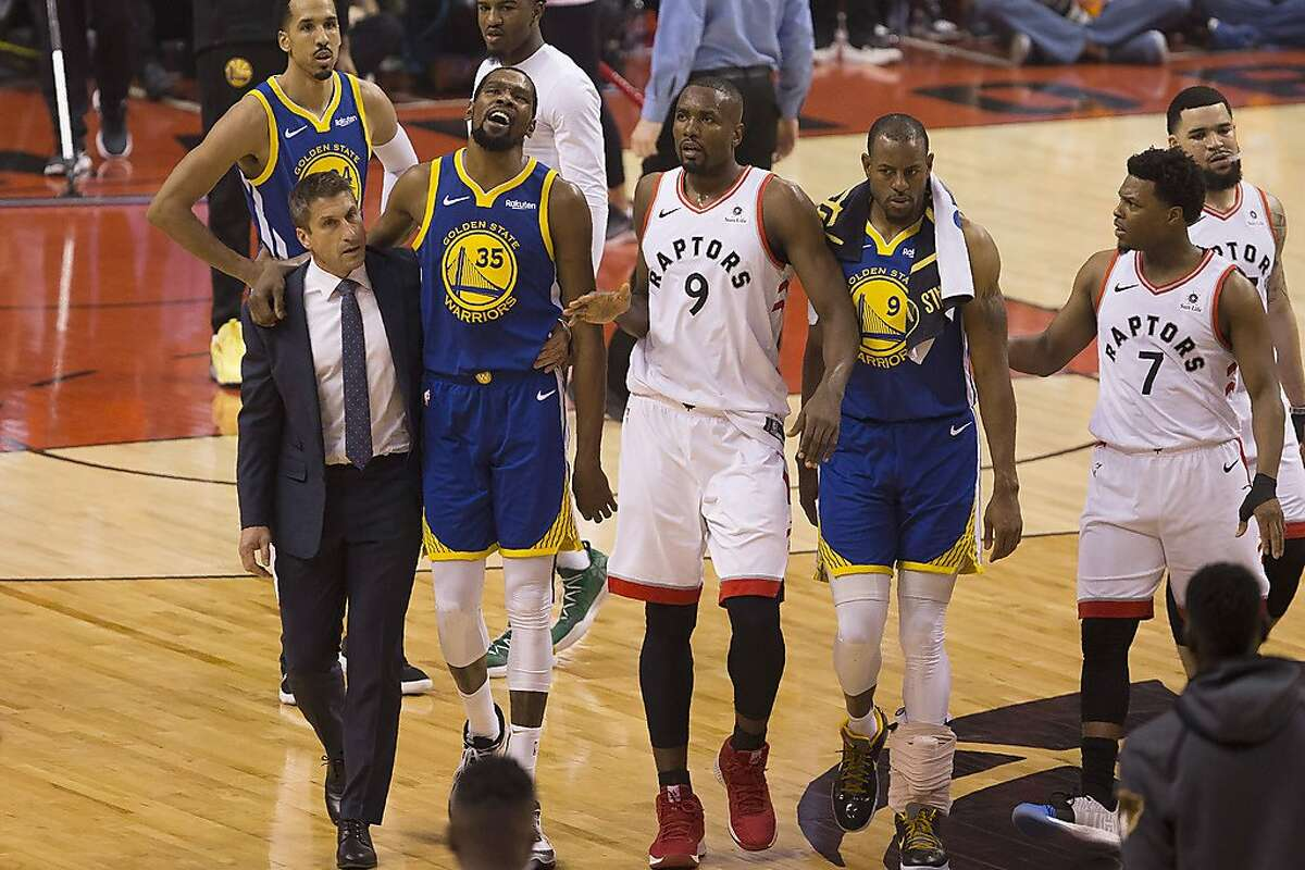 FILE - In this Monday, June 10, 2019 file photo, Golden State Warriors forward Kevin Durant (35) walks off the court after sustaining an injury as he is accompanied by Toronto Raptors center Serge Ibaka (9) and Warriors forward Andre Iguodala (9) and guard Kyle Lowry (7) during first-half basketball action in Game 5 of the NBA Finals in Toronto. On Friday, June 14, 2019, The Associated Press found that a video circulating on the internet that appeared to show fans in a Toronto bar cheering as Durant's injury is shown on a large TV screen was deceptively altered, with the Durant injury image inserted into unrelated footage of cheering soccer fans. (Chris Young/The Canadian Press via AP)