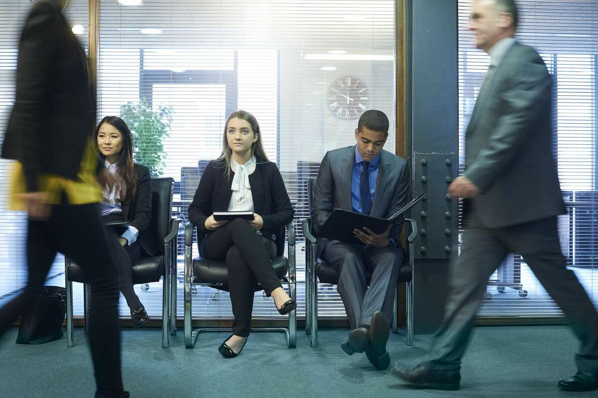 three recent graduate interview candidates wait nervously in the reception of an office building. members of staff walk past the nervous trio and they conduct their work .