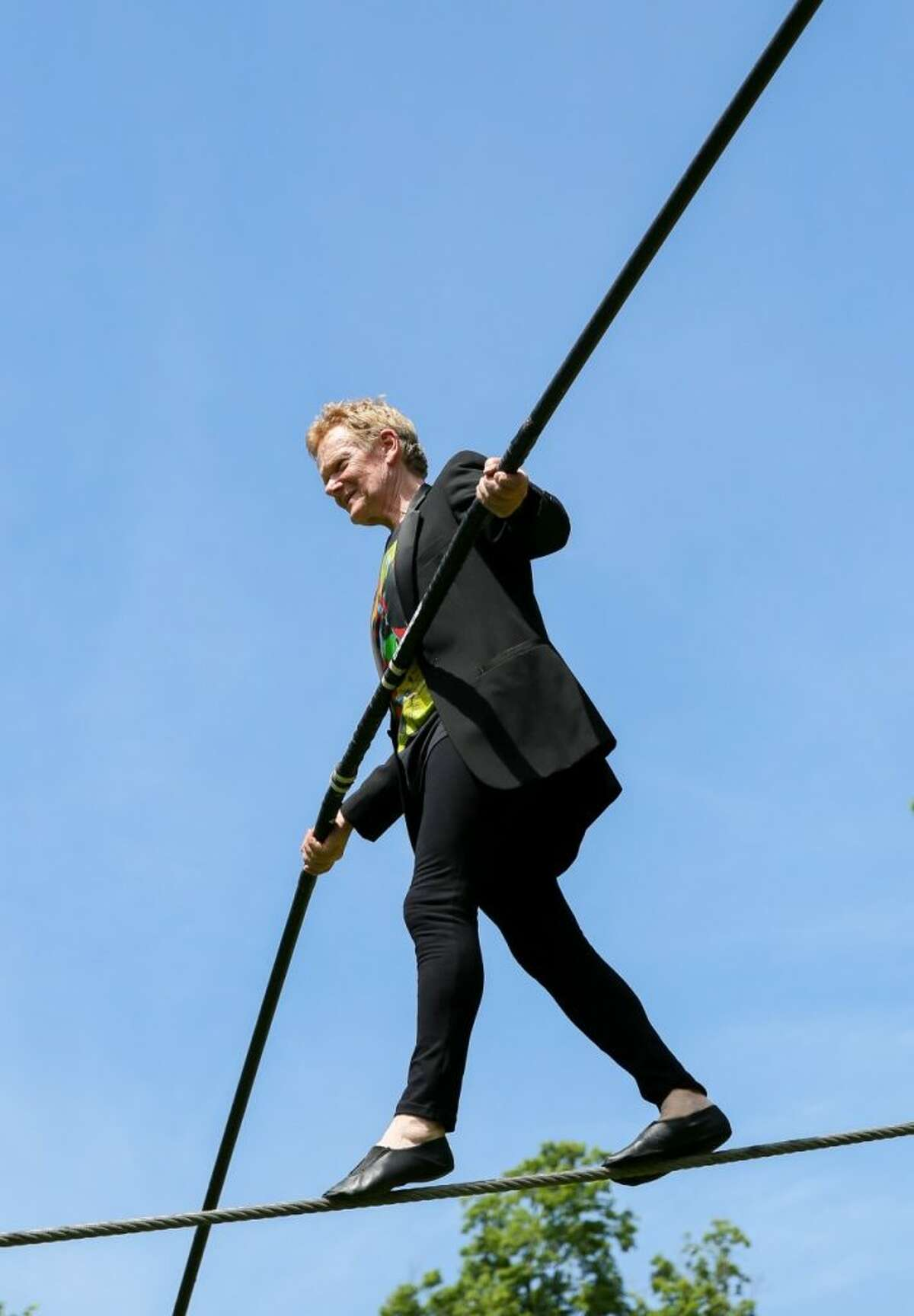 Philippe Petit on a hire wire attached to the roof of the Glass House. - Contributed photo
