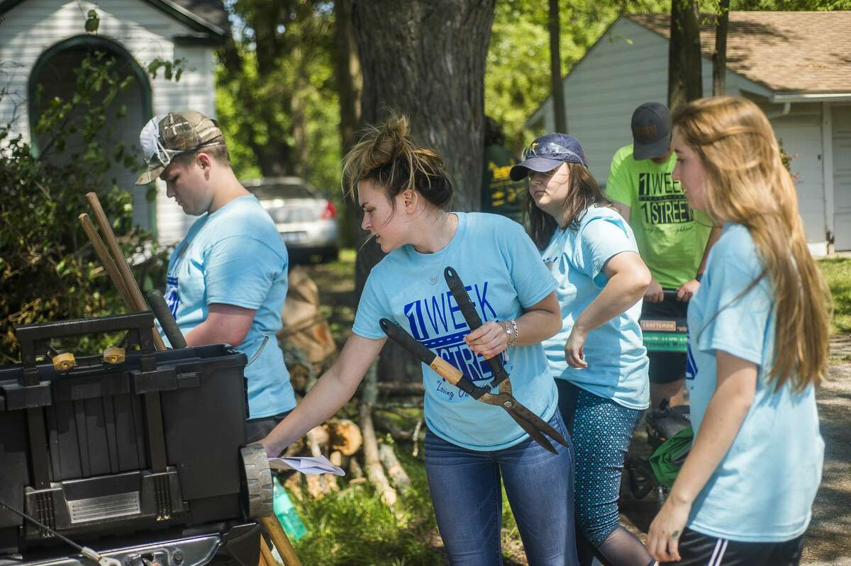 Members of the H. H. Dow High School robotics team work to clean up the exterior of a home as part of the One Week One Street neighborhood revitalization effort on Tuesday, June 25, 2019 in Saginaw. (Katy Kildee/kkildee@mdn.net)