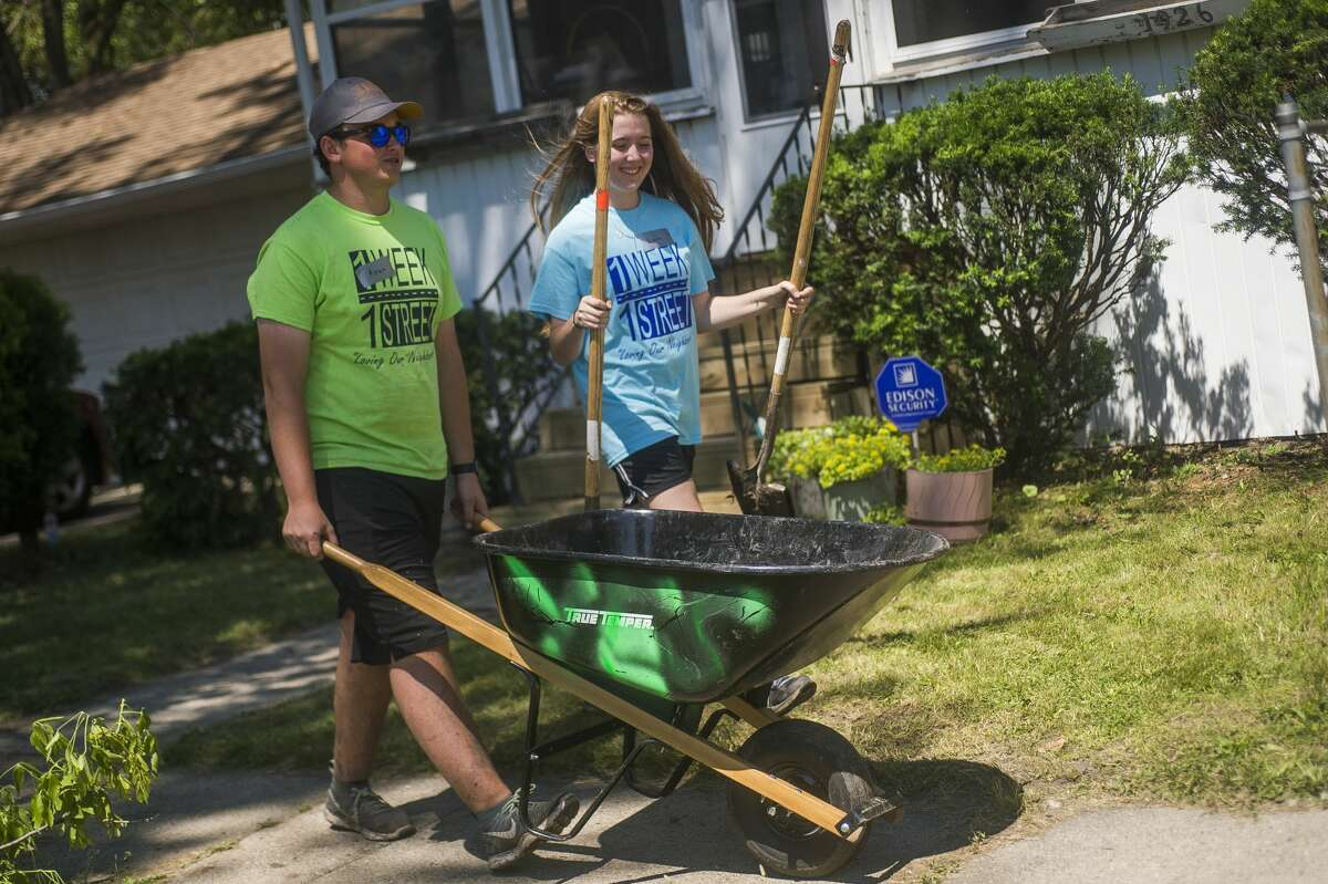Members of the H. H. Dow High School robotics team Ryan Collick, 17, left, and Lauren Woods, 18, right, carry equipment while working to clean up the exterior of a home as part of the One Week One Street neighborhood revitalization effort on Tuesday, June 25, 2019 in Saginaw. (Katy Kildee/kkildee@mdn.net)