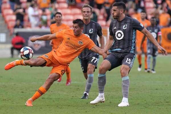 Houston Dynamo Ronaldo Pena kicks the ball past Minnesota United FC Michael Boxall during the first half of game at BBVA Stadium Tuesday, June 18, 2019, in Houston.