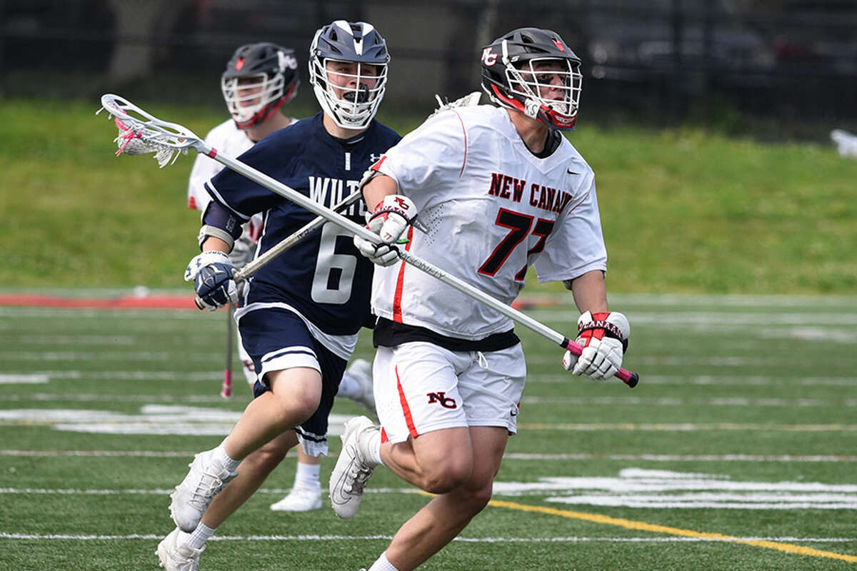 New Canaan's Walker Ker (77) carries the ball through the midfield with Wilton's John Kauffman (6) in pursuit during the Class L boys lacrosse quarterfinals at Dunning Field in New Canaan on Saturday, June 1, 2019. - Dave Stewart/Hearst Connecticut Media