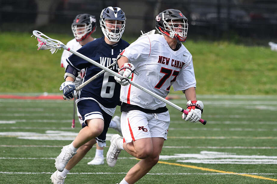 New Canaan's Walker Ker (77) carries the ball through the midfield with Wilton's John Kauffman (6) in pursuit during the Class L boys lacrosse quarterfinals at Dunning Field in New Canaan on Saturday, June 1, 2019. — Dave Stewart/Hearst Connecticut Media / Hearst Connecticut Media