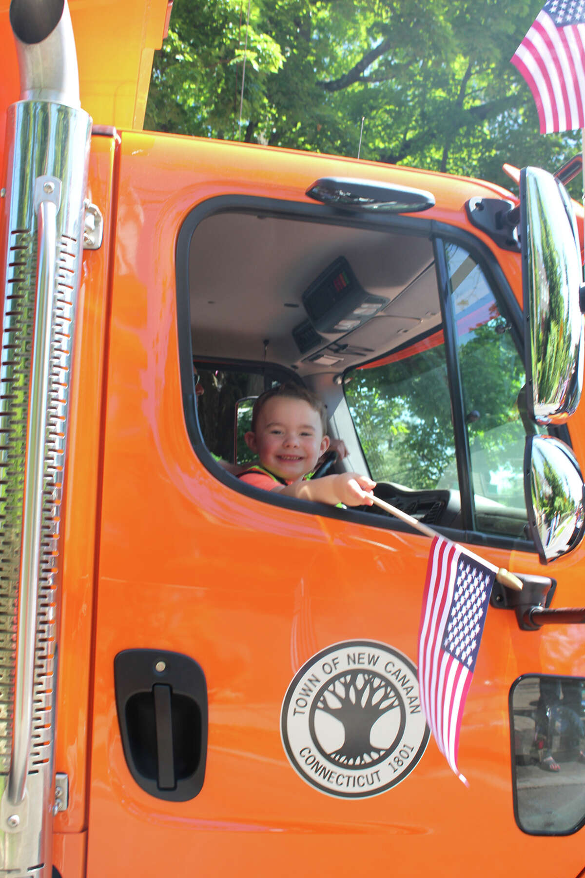 Mark Boice waves a flag from the cab of a Department of Public Works dump truck, driven by his father Louie, during the 2019 New Canaan Memorial Day Parade on Monday,May 27. John Kovach photo