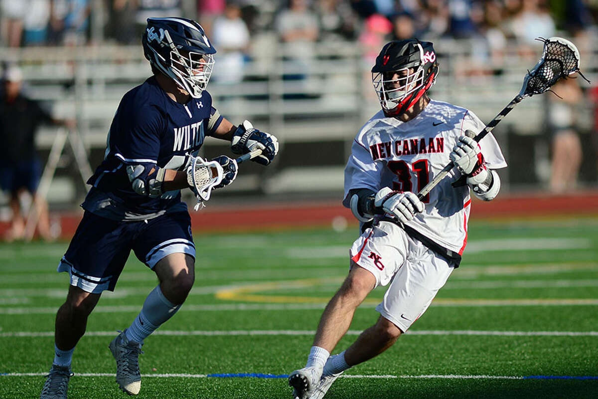 Wilton's Dylan Kennedy and New Canaan's Ryan Caione go head to head in the FCIAC boys lacrosse championship game on Friday, May 24, at Brien McMahon High School. - Erik Trautmann/Hearst Connecticut Media