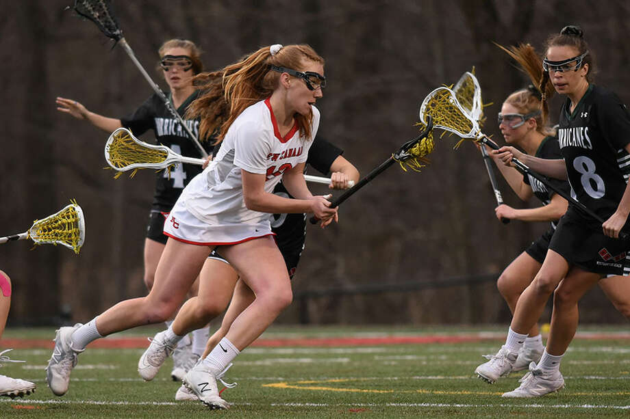 New Canaan's Jane Charlton (19) battles the Westhampton Beach defense during a girls lacrosse game at Dunning Field on Friday. — Dave Stewart/Hearst Connecticut Media / Hearst Connecticut Media