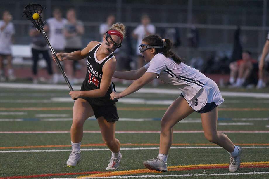 New Canaan's Campbell Connors (14) drives while Staples' Samantha Pacilio (8) defends during the FCIAC girls lacrosse semifinals at Norwalk's Testa Field on Monday, May 20, 2019. — Dave Stewart/Hearst Connecticut Media / Hearst Connecticut Media