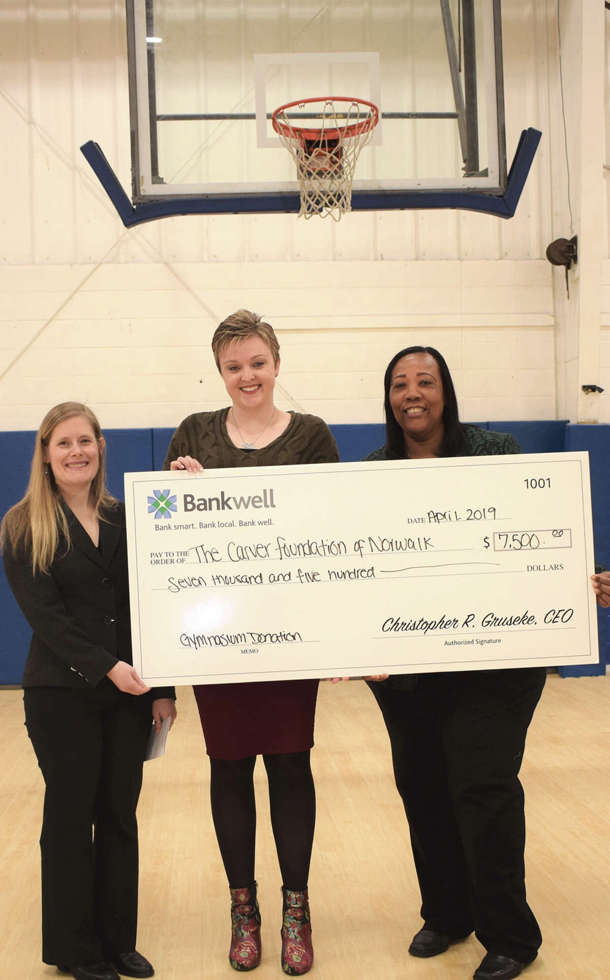 Nikki LaFaye, director of philanthropy at The Carver Foundation of Norwalk, Lucy French, assistant vice president and marketing manager at Bankwell, and Novelette Peterkin, CEO of the Carver Foundation of Norwalk, announce a $5,000 donation toward a gym expansion that will allow basketball programs to grow. Bankwell / Contributed photo