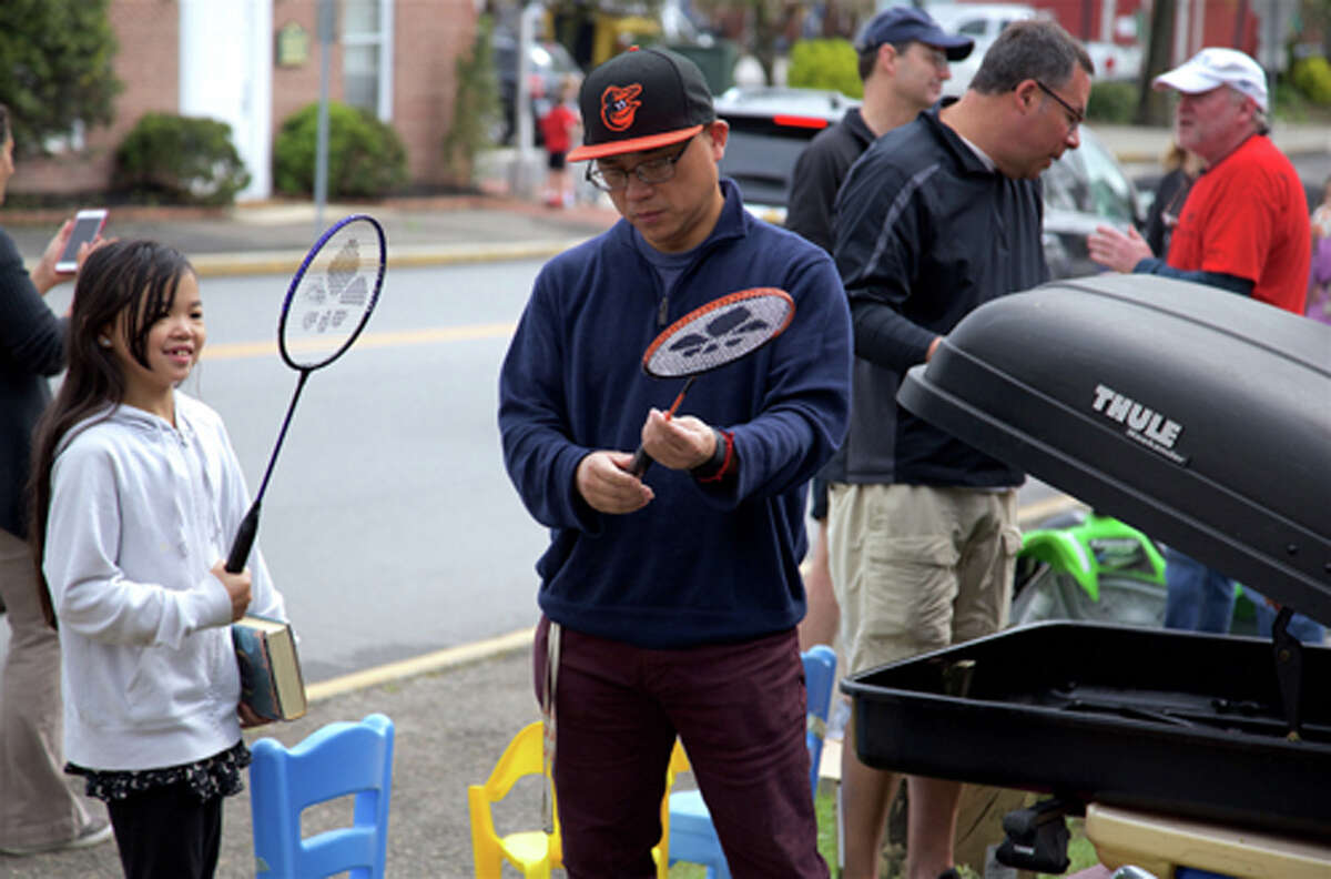 John Xu of New Canaan and his daughter Alina, 8, try out some badminton rackets at Boy Scout Troop 70's annual tag sale. Jarret Liotta / For Hearst Connecticut Media
