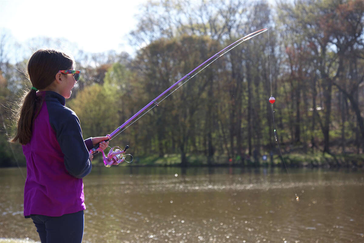 Abigail Greenhut, 9, of New Canaan, fishes on Mill Pond during the annual fishing derby, which was postponed to Saturday, April 27. Jarret Liotta / For Hearst Connecticut Media
