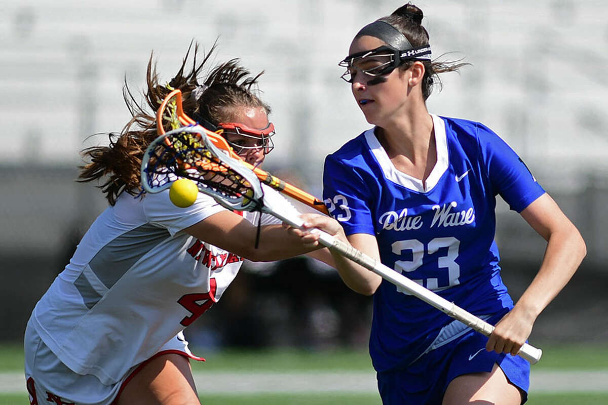 New Canaan's Kendall Patten (4) knocks the ball away from Darien's Maddie Joyce (23) as Darien takes on New Canaan on Saturday at Dunning Field. - Erik Trautmann/Hearst Connecticut Media