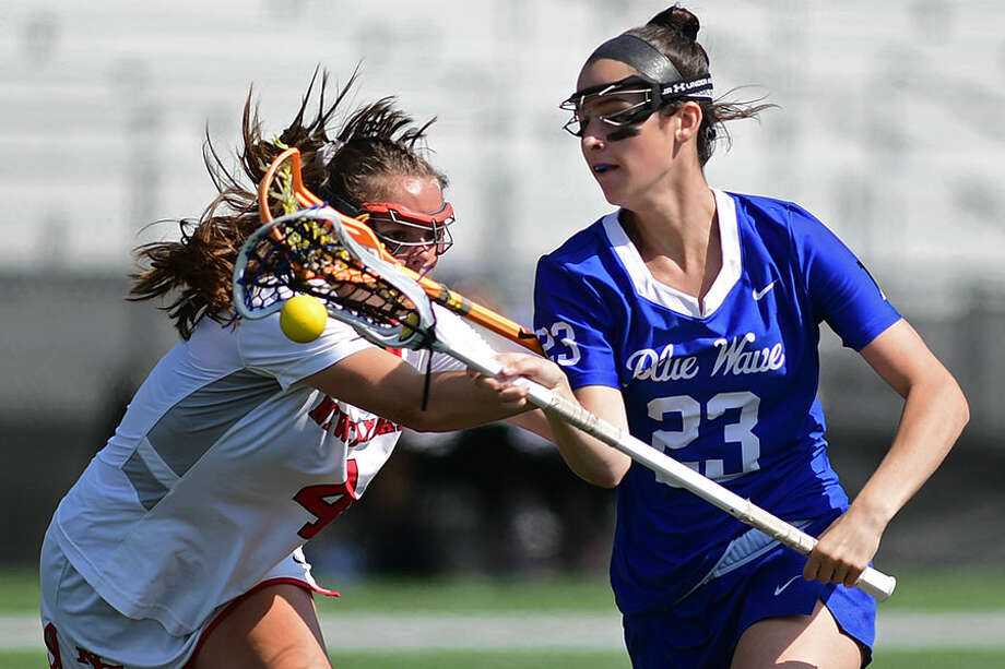 New Canaan's Kendall Patten (4) knocks the ball away from Darien's Maddie Joyce (23) as Darien takes on New Canaan on Saturday at Dunning Field. — Erik Trautmann/Hearst Connecticut Media / Norwalk Hour