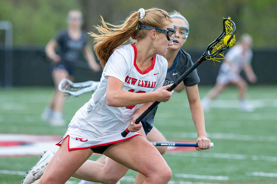 New Canaan's Jane Charlton looks to get past a Wilton defender during a girls lacrosse game Tuesday. — Gretchen McMahon photo/For Hearst Connecticut Media