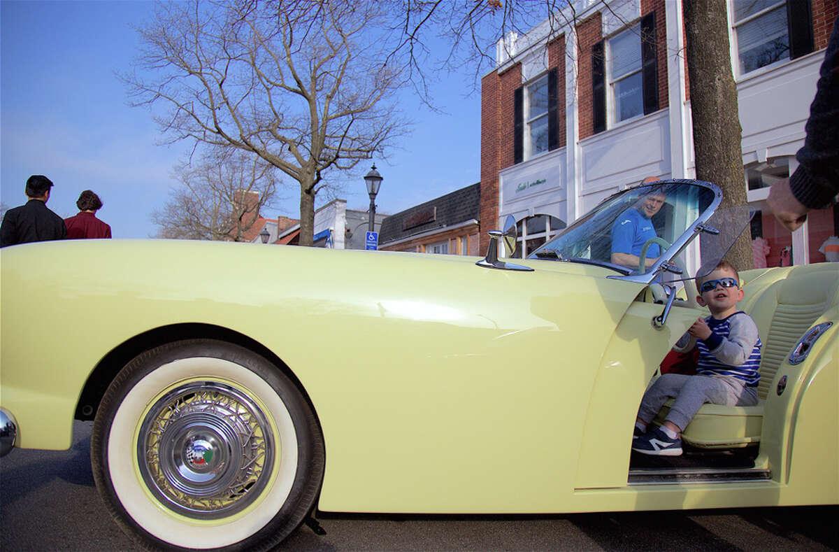 Gabriel Rutledge, 2, of Greenwich, gets a taste of driving a 1954 Kaiser Darren during Caffeine and Carburetors on Elm Street Sunday, April 14, 2019. - Jarret Liotta / For Hearst Connecticut Media