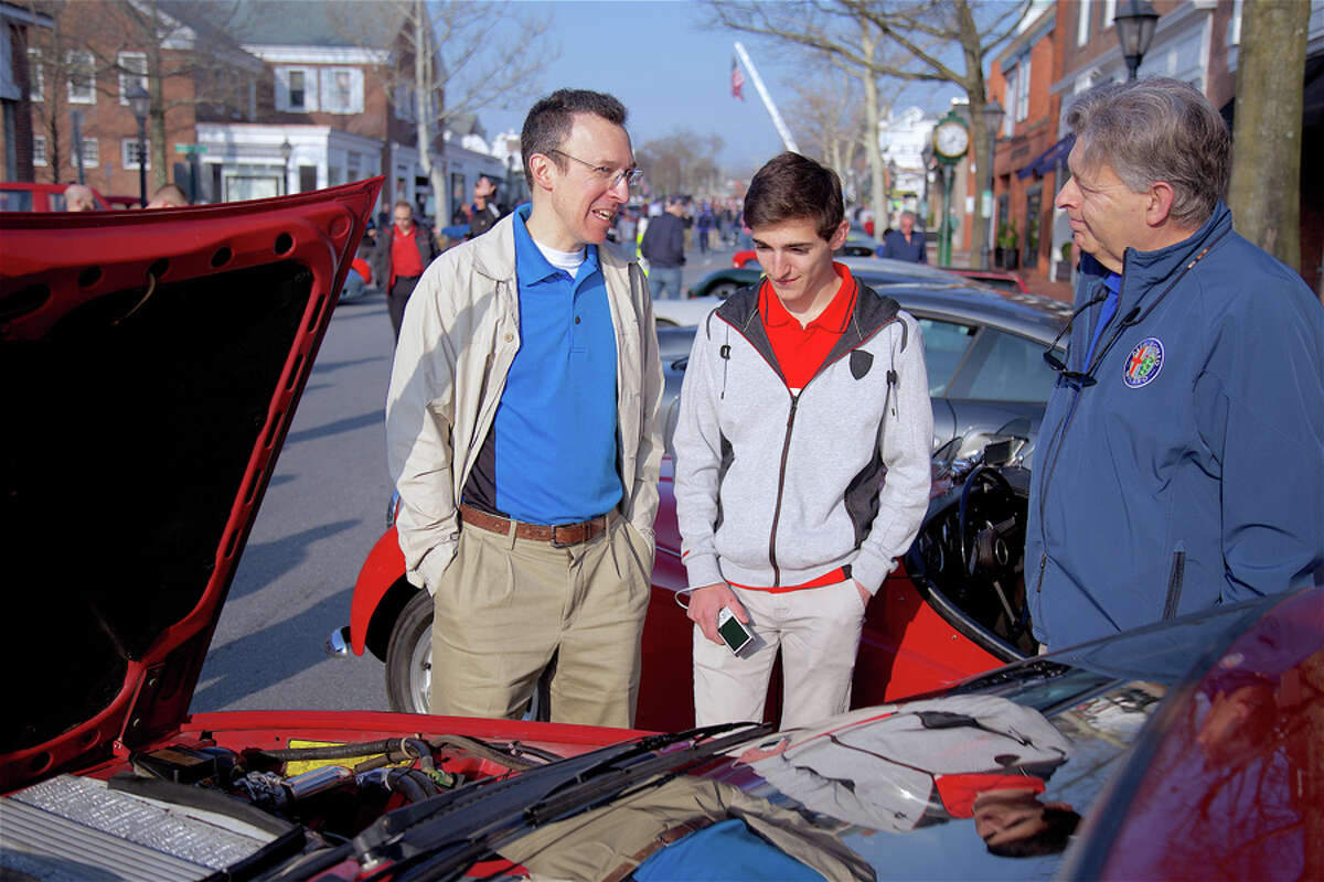 Nick Bulzacchelli of Chester, N.J., left, and his son, Michael, talk cars with Michael Davias of Stamford at Caffeine and Carburetors April 14, 2019 on Elm Street. - Jarret Liotta / For Hearst Connecticut Media