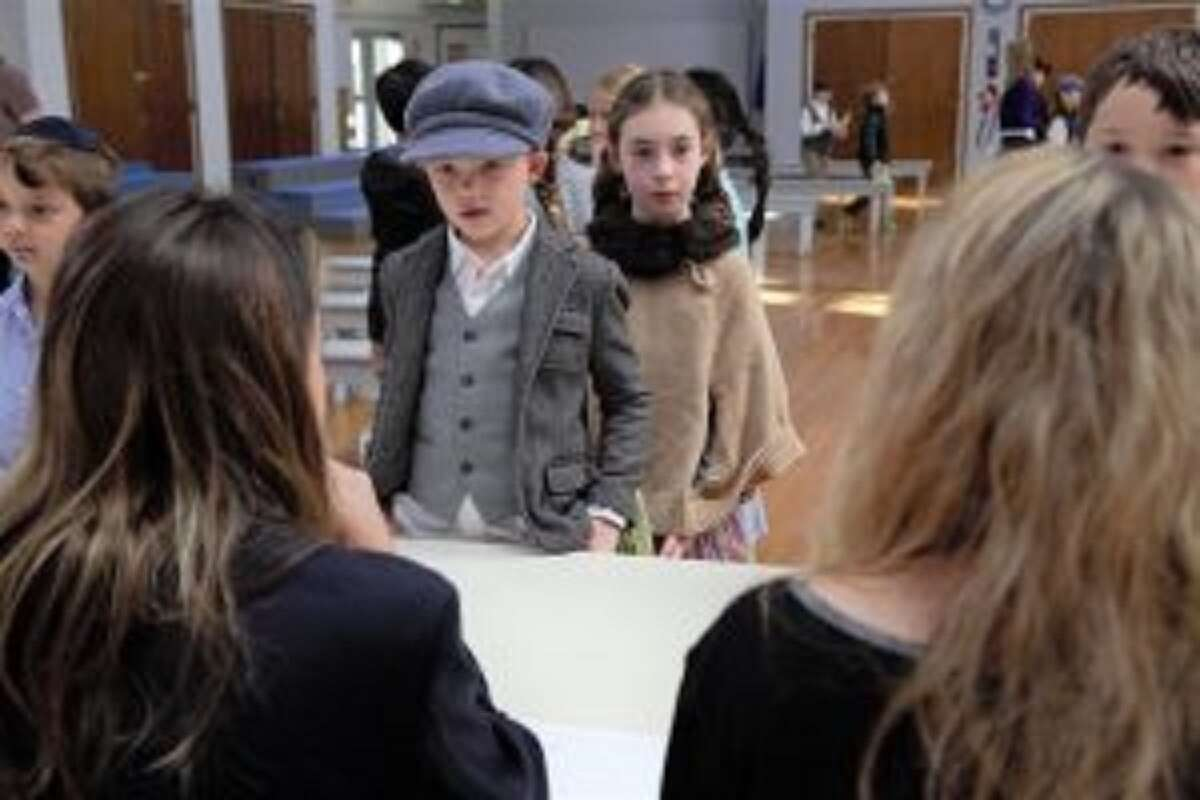 Thanos Ghoussias of Stamford and Eva Mackenzie of Darien, third graders at New Canaan Country School, recreate the journey through Ellis Island once faced by immigrants. - Contributed photo