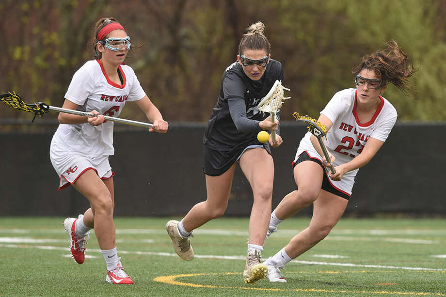 New Canaan's Natalie Lopez (23) knocks the ball away from Henna Brennan (2) of Longmeadow, Mass., as New Canaan's Kaleigh Harden (6) also defends during Saturday's girls lacrosse game at Dunning Field. — Dave Stewart/Hearst Connecticut Media / Hearst Connecticut Media