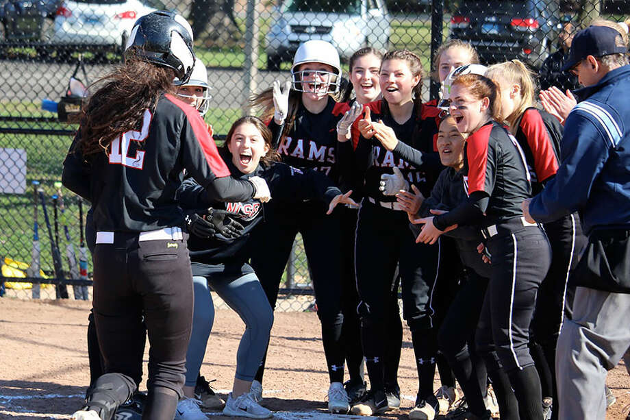 The New Canaan Rams greet senior Kara Fahey at home plate after one of her two home runs during a 15-2 win over Bridgeport Central in Waveny Park on Tuesday. — Terry Dinan photo / Hearst Connecticut Media