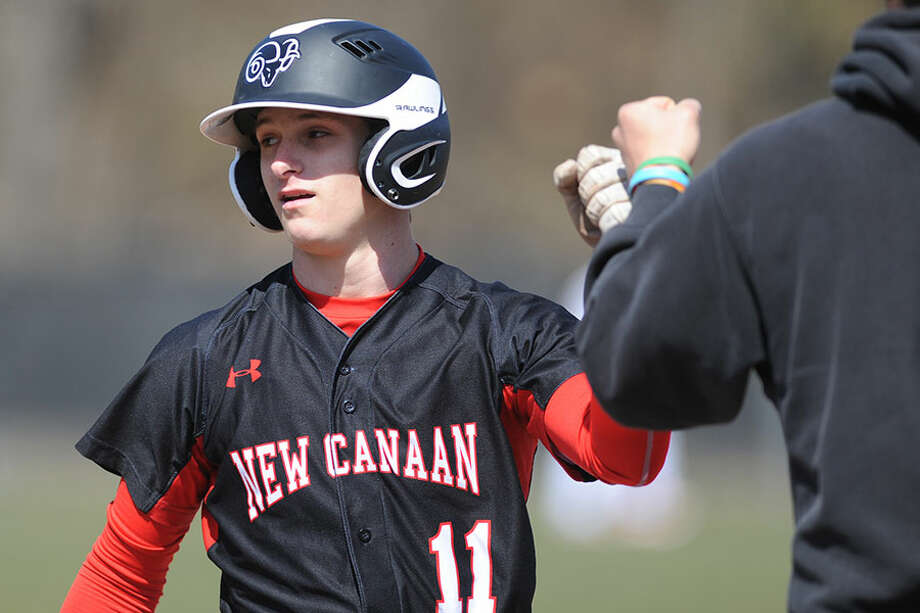 New Canaan's Frank Ramppen gets congratulated at first base after a hit last season. Ramppen was 3-for-3 during the Rams' win over Central on Tuesday. — Tyler Sizemore/Hearst Connecticut Media / Greenwich Time