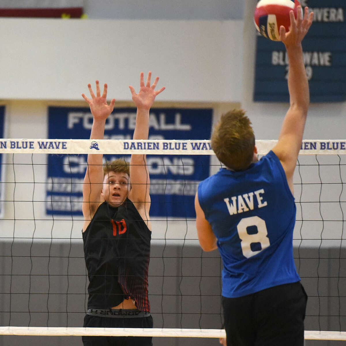 New Canaan's Gavin Bramwit (10) goes up to defend as Darien's Tyler Herget (8) hits a shot during a boys volleyball match on Wednesday. - Dave Stewart/Hearst Connecticut Media