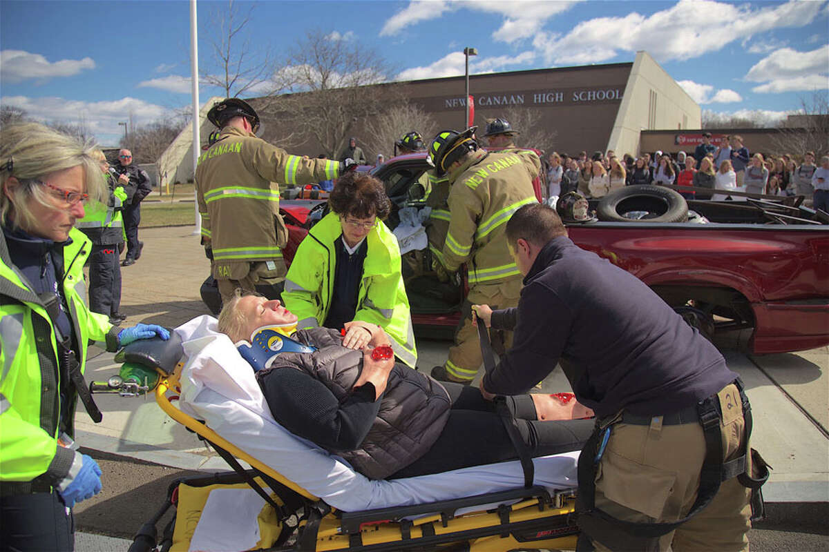 CERT member Maria Crocitto posed as a victim during a mock crash Monday, April 1, at New Canaan High School, demonstrating the dangers of distracted driving. - Jarret Liotta / For Hearst Connecticut Media