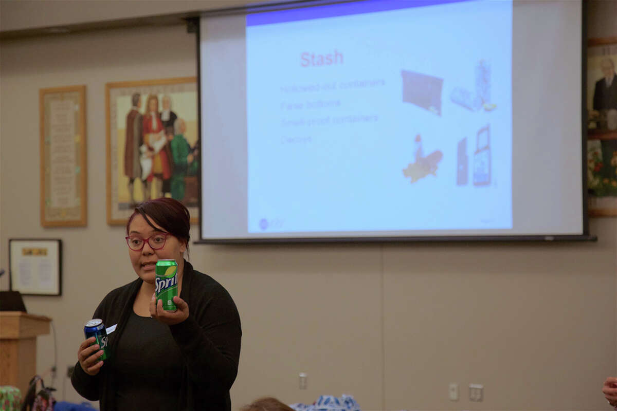 Denique Weidema-Lewis, director of prevention for Positive Directions, compares a real soda can in her left hand with a fake