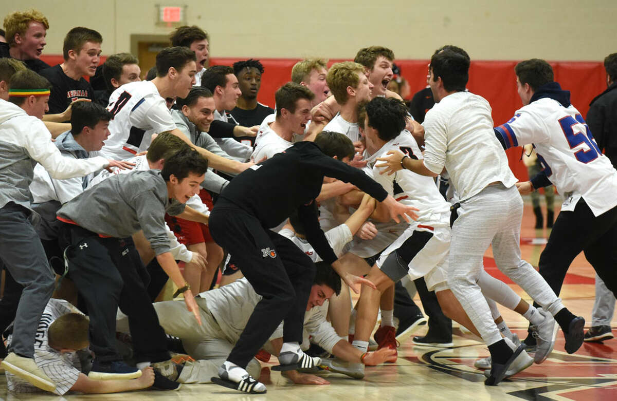 The New Canaan Rams and some of their fans celebrate on the court after beating Stamford 52-49 at New Canaan High School on Thursday, Jan. 10. - Dave Stewart/Hearst Connecticut Media